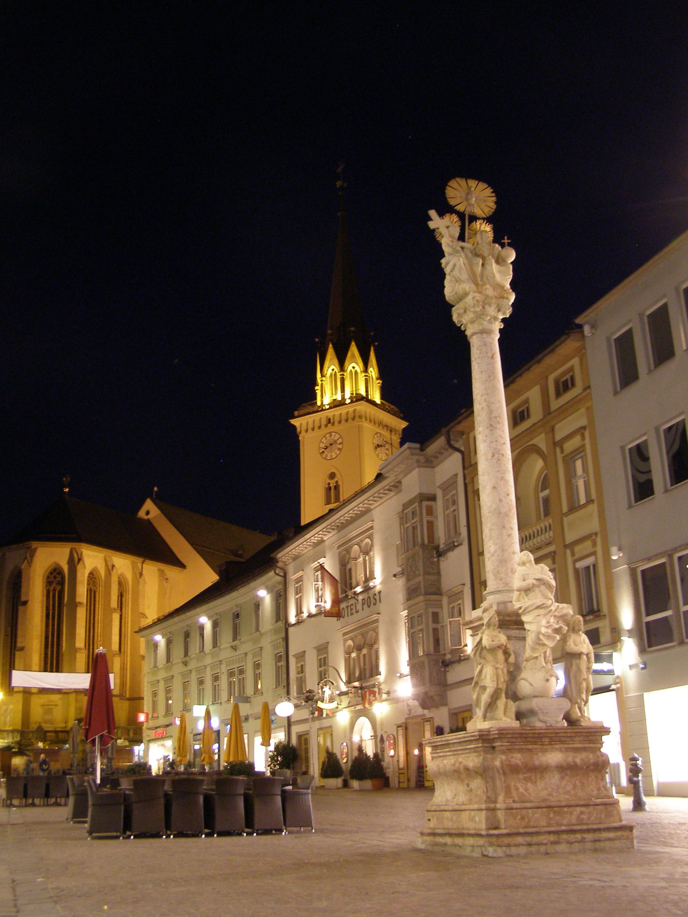 Villach main square Hauptplatz at night with the Holy Trinity column and the church of St. Jacob