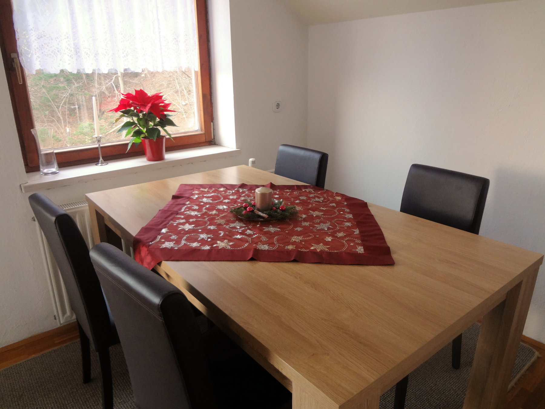 Holiday decorations and a poinsettia in the dinning area of the Fine Stay Apartment in Slovenia