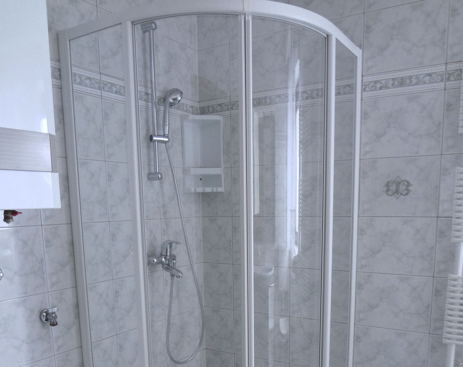 A glass shower stall in the bathroom of the Fine Stay Bled apartment in Lake Bled, Slovenia