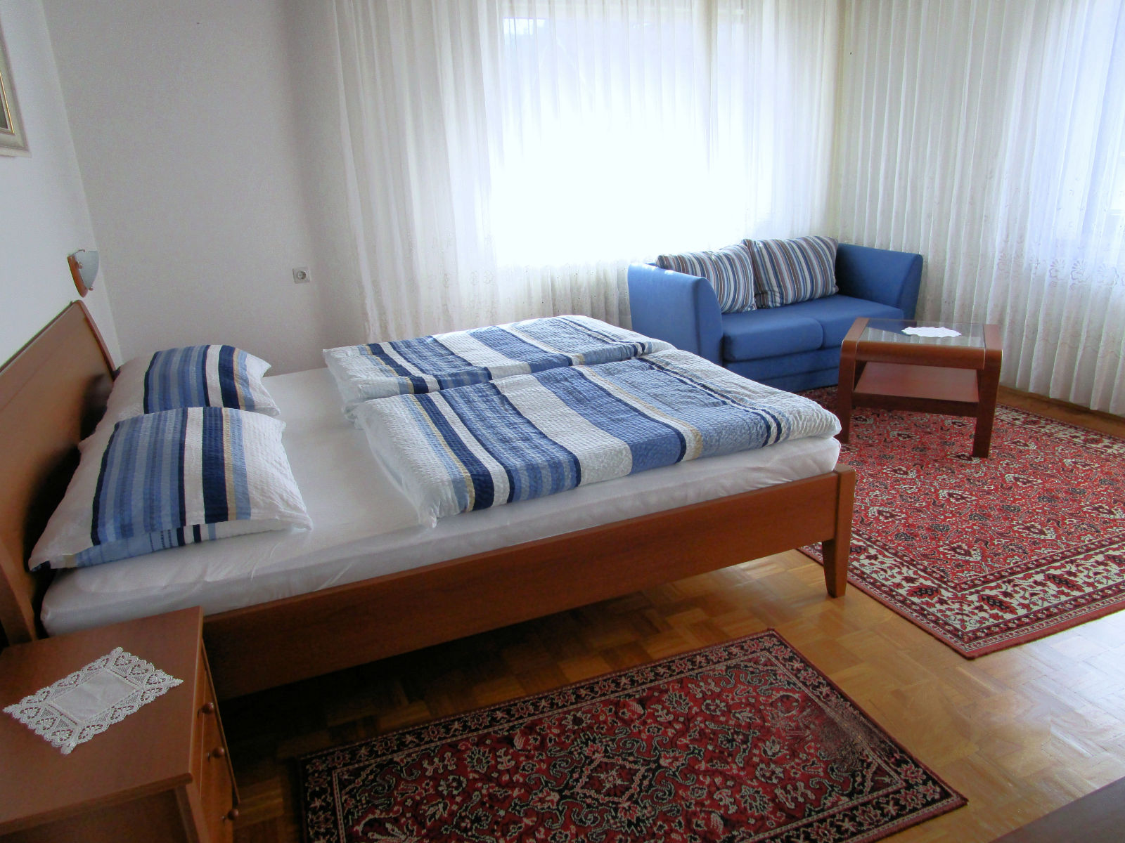 A king size bed and sofa in the first bedroom of the Fine Stay apartment in Lake Bled, Slovenia