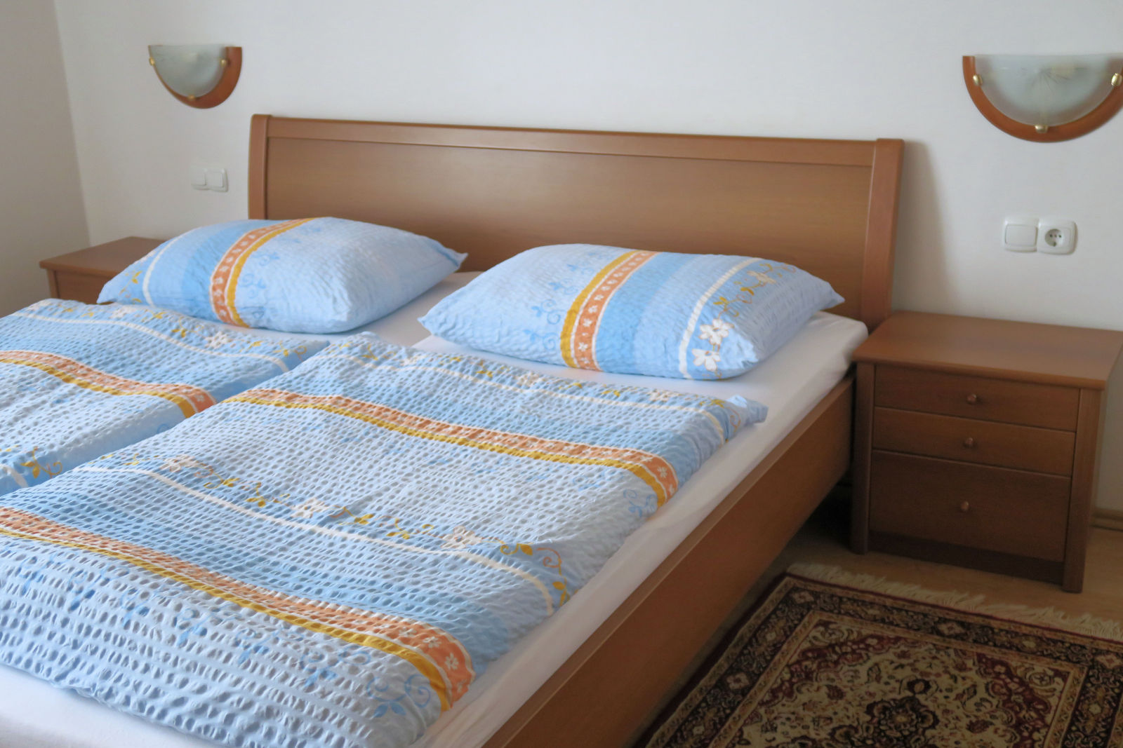 Double bed and and two nightstands in the second bedroom of the Fine Stay Bled apartment in Lake Bled, Slovenia