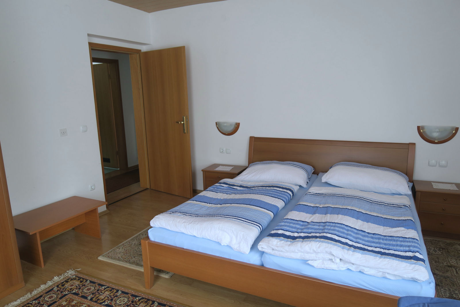 A large double bed and two nightstands in the first bedroom of the Fine Stay Bled apartment in Lake Bled, Slovenia