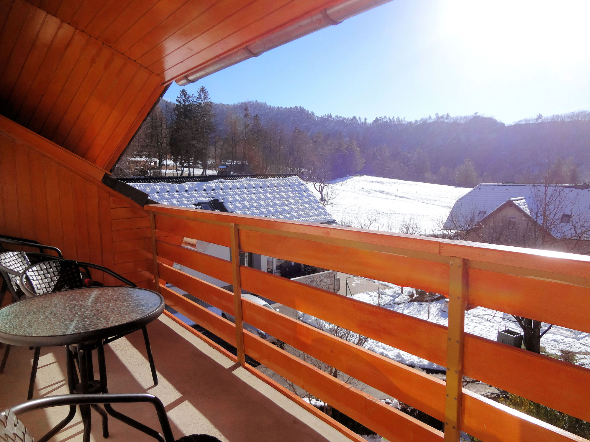 A wintry view of the snow covered pasture from the balcony of Apartments Fine Stay