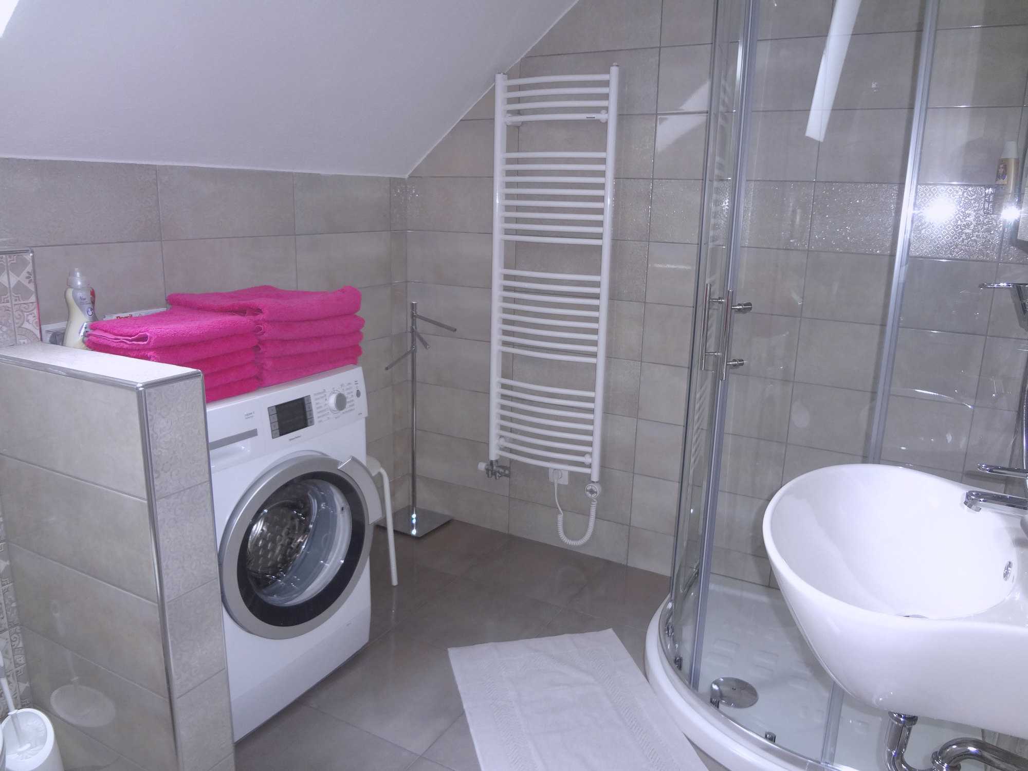 A glass shower stall and a washing machine in the bathroom of Apartments Fine Stay in Slovenia