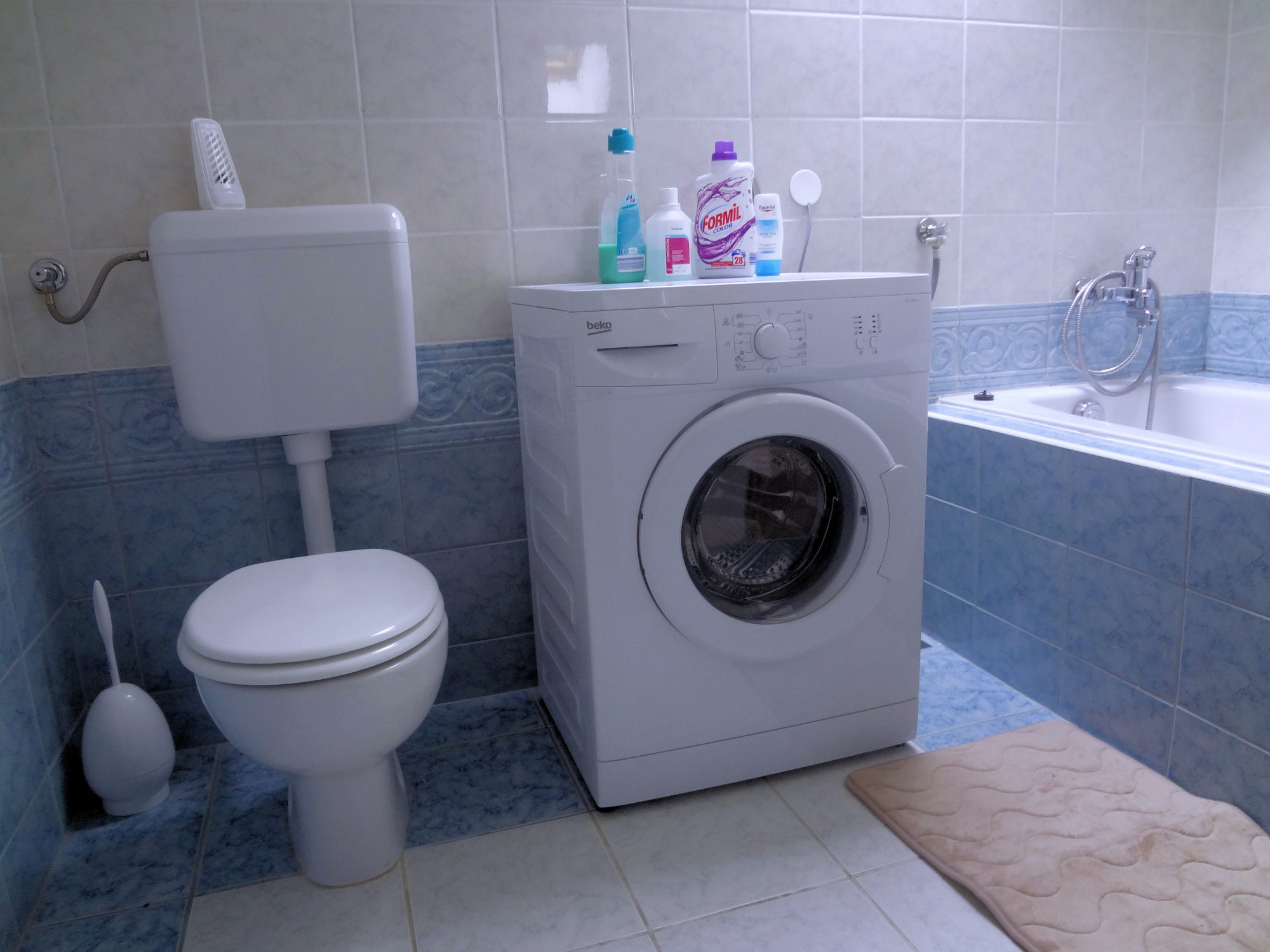 A bathtub, washing machine and toilet in the bathroom of Apartments Fine Stay in the Bled area of Slovenia