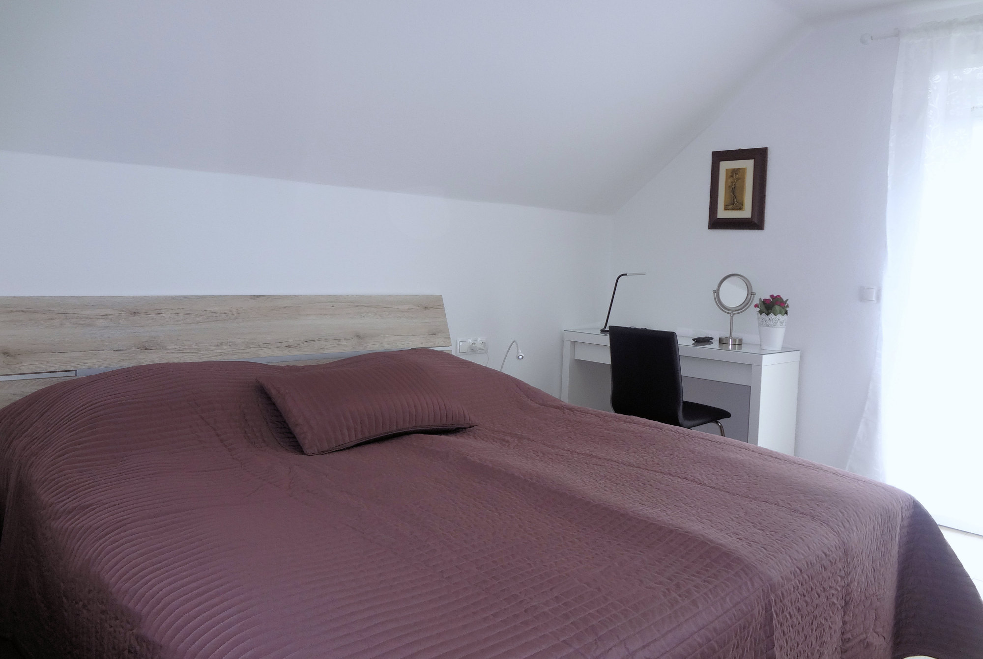 A king size double bed and a work desk in the bedroom of Fine Stay Apartment in Slovenia