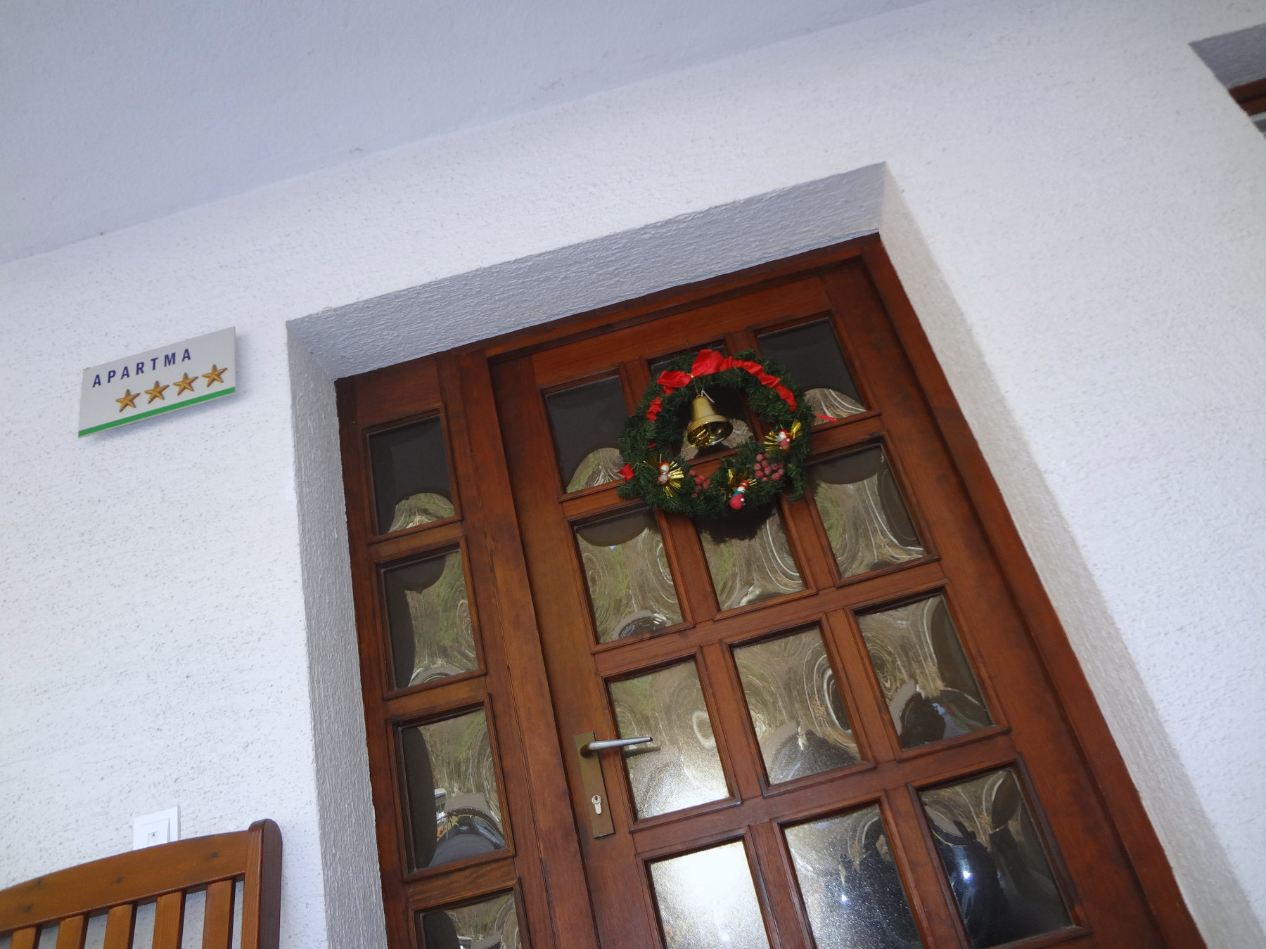 A Christmas wreath hanging on the front door of Fine Stay Apartments